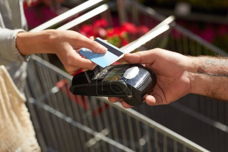 Photo pour Gros plan d'une cliente méconnaissable détenant une carte bancaire tout en payant via NFC dans une plantation de fleurs à l'extérieur, espace de copie - image libre de droit