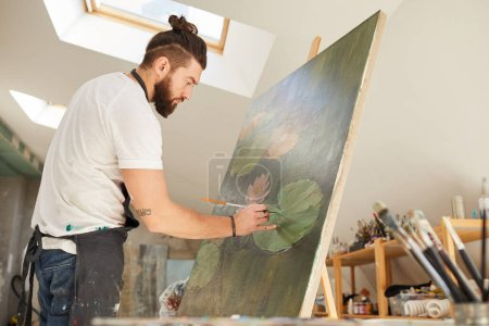 Photo for Side view portrait of talented male artist painting picture on easel while working in spacious art studio lit by sunlight, copy space - Royalty Free Image