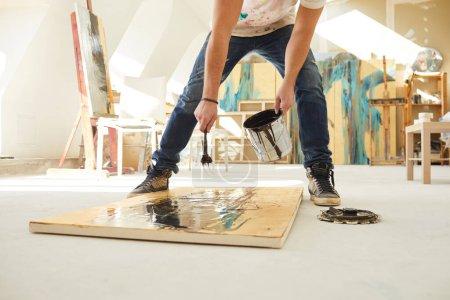 Photo pour Portrait en coupe basse d'un artiste contemporain méconnaissable étalant de la peinture sur la peinture tout en travaillant sur une image abstraite dans un studio d'art éclairé par la lumière du soleil, espace de copie - image libre de droit
