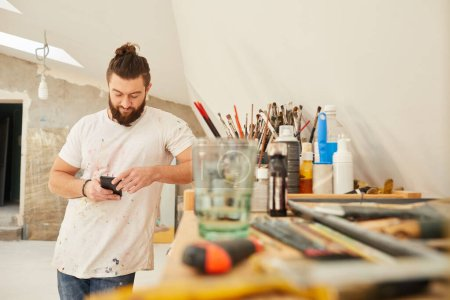 Photo for Waist up portrait of contemporary bearded artist using smartphone while standing in spacious art studio, copy space - Royalty Free Image