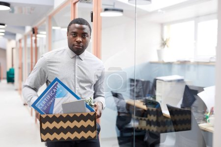Photo for Waist up portrait of young African-American man holding box of personal belongings after quitting job in office, copy space - Royalty Free Image