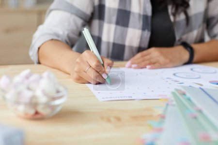 Photo for Close up of young mixed-race woman drawing graphs and charts while planning project at home, copy space - Royalty Free Image