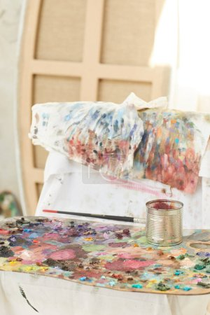 Photo for Vertical background image of colorful artists palette covered with paint blots resting by easel in art studio lit by sunlight, copy space - Royalty Free Image