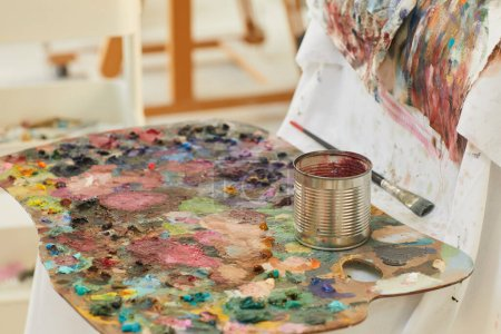 Photo for Background image of colorful artists palette covered with paint blots resting by easel in art studio lit by sunlight, copy space - Royalty Free Image