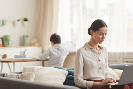 Photo for Warm-toned portrait of elegant young woman using laptop while working at home with her son studying in background, copy space - Royalty Free Image