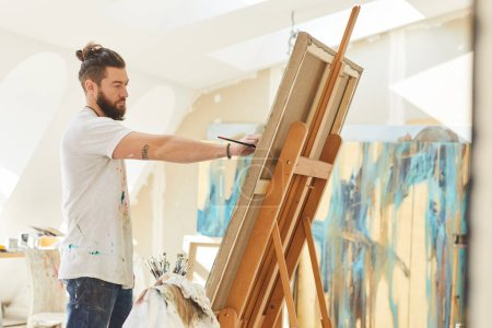 Photo for Side view portrait of contemporary male artist painting picture on easel while working in sunlit art studio, copy space - Royalty Free Image