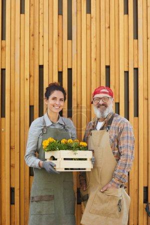 Photo pour Portrait vertical de deux jardiniers joyeux tenant des fleurs tout en se tenant par fond en bois graphique - image libre de droit