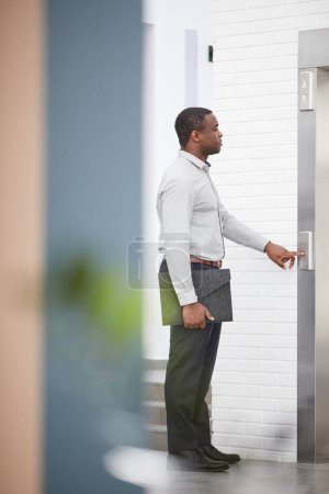 Photo pour Vue latérale pleine longueur portrait de jeune homme d'affaires afro-américain appuyant sur le bouton d'ascenseur dans le hall de bureau, espace de copie - image libre de droit