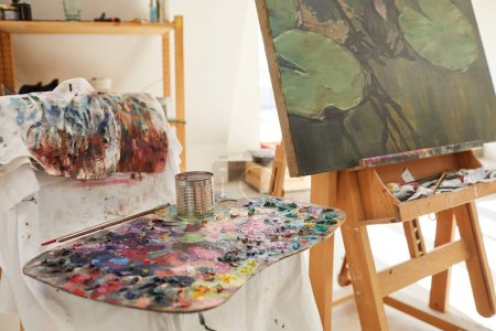 Photo for Close up of colorful artists palette covered with paint on tool stand in art studio, easel with painting in background, copy space - Royalty Free Image