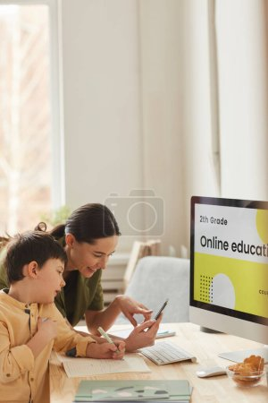 Photo for Vertical portrait of smiling young mother helping little boy studying online at home, copy space - Royalty Free Image