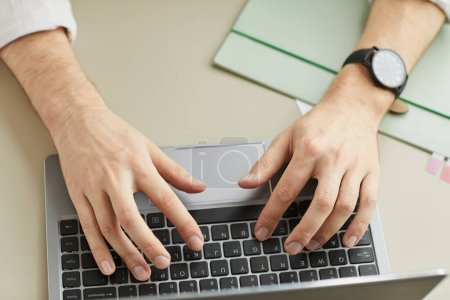 Photo for Above view close up of unrecognizable man using laptop, focus on male hands typing at keyboard, copy space - Royalty Free Image