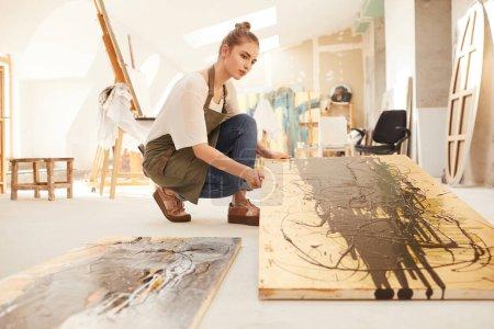Photo pour Portrait d'artiste féminine moderne aux tons chauds tenant une peinture abstraite tout en étant assise sur le sol dans un studio d'art spacieux éclairé par la lumière du soleil, espace de copie - image libre de droit
