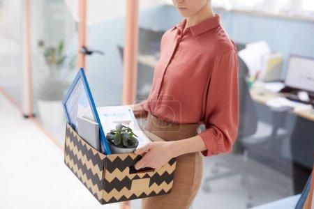 Foto de Retrato de sección media de una joven empresaria sosteniendo una caja de pertenencias personales después de ser despedida del trabajo en la oficina, espacio para copias - Imagen libre de derechos