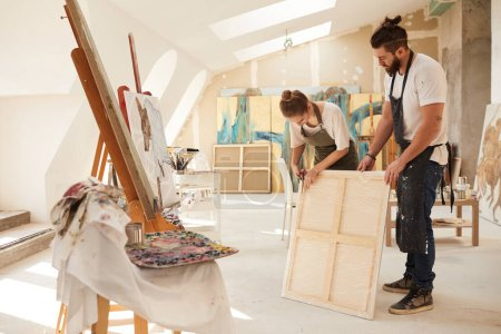 Photo for Full length portrait of two contemporary artists wrapping painting for shipping while standing in spacious art studio lit by sunlight, copy space - Royalty Free Image