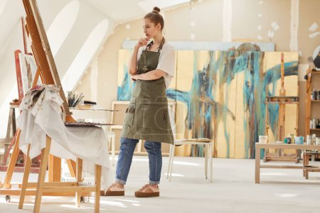 Photo for Full length portrait of modern female artist looking at painting while working in art studio lit by sunlight, copy space - Royalty Free Image