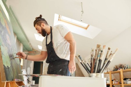 Photo for Side view portrait of contemporary bearded artist painting picture on easel with great focus and attention while standing in spacious attic art studio, copy space - Royalty Free Image