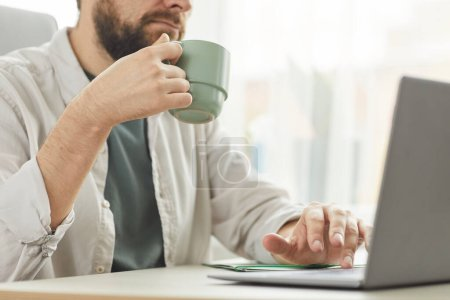 Photo for Cropped portrait of bearded adult man drinking coffee while using laptop at home office, copy space - Royalty Free Image