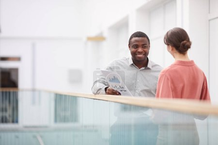 Photo for Waist up portrait of smiling African-American man holding documents while talking to female colleague at balcony in office building, copy space - Royalty Free Image