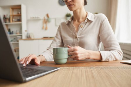 Photo for Cropped portrait of elegant businesswoman drinking coffee while using laptop at cozy home office workplace, copy space - Royalty Free Image