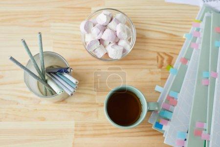Photo pour Vue du haut vers le bas du travail ou de l'étude des fournitures avec tasse à thé sur fond de table en bois, espace de copie - image libre de droit