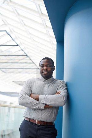 Foto de Retrato vertical de la cintura hacia arriba del exitoso hombre de negocios afroamericano mirando a la cámara mientras se apoya contra la pared en el moderno edificio de oficinas, espacio para copiar - Imagen libre de derechos