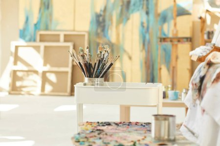 Photo for Background image of set of paintbrushes and tools resting by easel in empty art studio lit by sunlight, copy space - Royalty Free Image