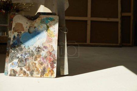 Photo pour Image de fond de palette d'artistes colorés éclairés par la lumière du soleil dans l'intérieur du studio d'art vide, espace de copie - image libre de droit