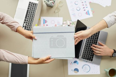 Photo for Top down view at two people handing folder across workplace table with laptops, copy space - Royalty Free Image