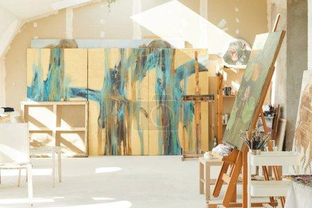 Photo pour Image de fond de studio d'art vide dans le grenier éclairé par la lumière du soleil, accent sur chevalet et peintures abstraites, espace de copie - image libre de droit