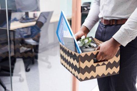 Photo pour Gros plan d'un homme afro-américain méconnaissable tenant une boîte d'effets personnels après avoir quitté son emploi, espace de copie - image libre de droit