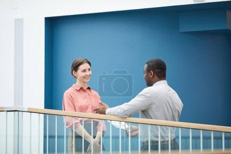 Photo pour Portrait taille haute de jeune femme d'affaires souriante parlant à un collègue afro-américain tout en se tenant sur un balcon contre un mur bleu, espace de copie - image libre de droit
