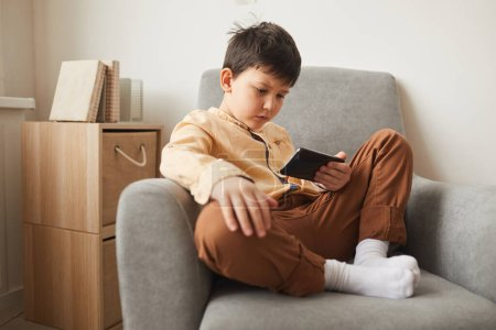 Photo for Full length portrait of cute boy sitting cross-legged in armchair and using smartphone, copy space - Royalty Free Image