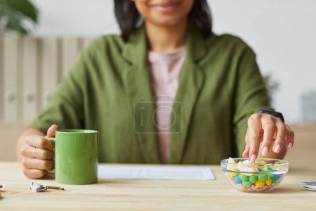 Photo for Cropped portrait of mixed-race young woman enjoying sweet gummy snacks while working from home, copy space - Royalty Free Image