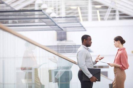 Foto de Retrato de vista lateral del exitoso hombre de negocios afroamericano que habla con una mujer joven mientras está de pie en el balcón en el interior del edificio de oficinas, espacio para copiar - Imagen libre de derechos