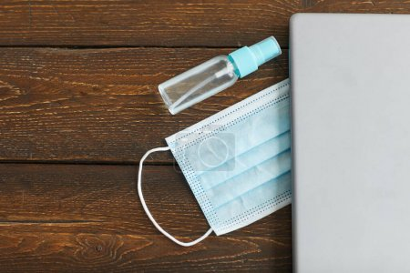 Photo for Close up of laptop, face mask and hand sanitizer over dark wooden background, quarantine home office workplace, copy space - Royalty Free Image