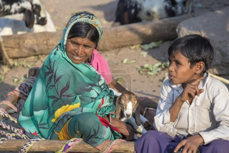 Photo for MANDU, INDIA - FEBRUARY 03, 2017 : An unidentified Indian family sits on the street with goatling. Poverty is a major issue in India - Royalty Free Image