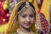 PUSHKAR, INDIA - NOVEMBER 16, 2018 : Indian young girl in the desert Thar on time Pushkar Camel Mela near holy city Pushkar, Rajasthan, India, close up portrait