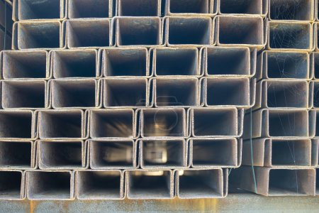 Photo for Rusty rectangular metal pipe in the packs are stored in the metal products warehouse, close up. Steel materials, construction supplies. - Royalty Free Image