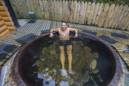 Man bathing in cast iron vat with mineral water co...