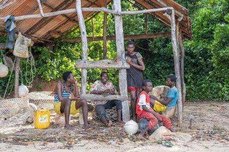 Photo pour Zanzibar, Tanzanie - 16 novembre 2019 : Des hommes et des garçons africains sont assis sous un auvent à l'ombre sur le rivage de l'île de Zanzibar, en Tanzanie, en Afrique de l'Est, gros plan - image libre de droit