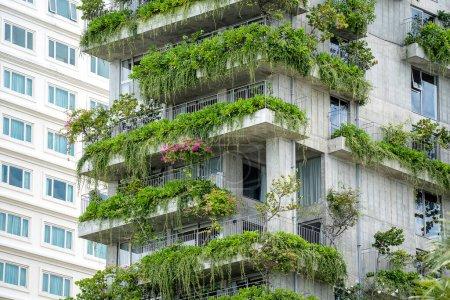 Photo pour Bâtiments écologiques façade avec des plantes vertes et des fleurs sur le mur de pierre de la façade de la maison dans la rue de la ville de Danang au Vietnam - image libre de droit