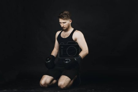 Photo for Portrait of a pensive man with boxing gloves on hands sitting on the floor in a studio with black background. - Royalty Free Image