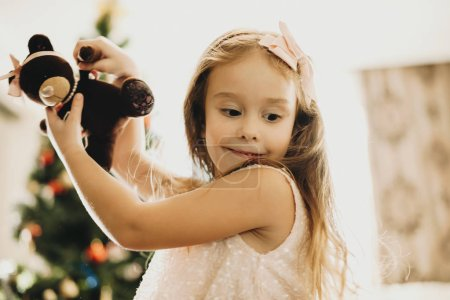 Side view of little excited girl in pink bow playing with teddy bear at home looking down