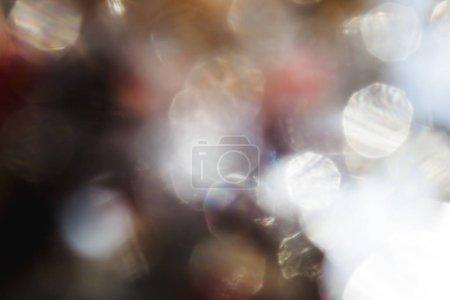 Closeup shot de taches floues de lumière dorée scintillante sur fond sombre Résumé