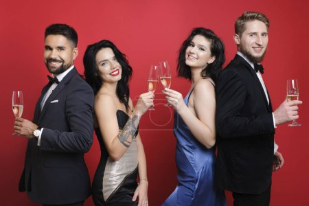 Side view of handsome guys in suits and attractive women in beautiful dresses holding glasses of champagne and smiling while standing on bright red background