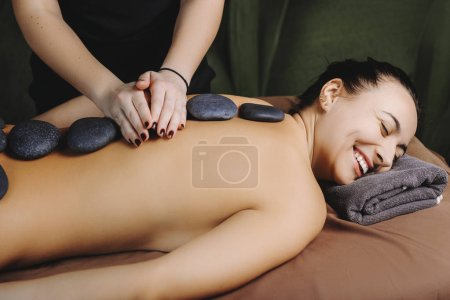 Photo pour Belle femme allongée sur un lit de massage sourire avec les yeux fermés, tandis que le masseur fait stone thérapie aux pierres volcaniques chaudes dans le centre de bien-être. - image libre de droit