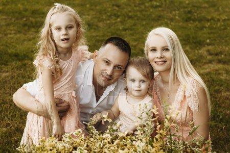 Foto de Retrato exterior de madre y padre con sus dos hijas pequeñas al aire libre. Mamá y papá abrazan a sus hijos mientras miran las cámaras sonrientes.. - Imagen libre de derechos