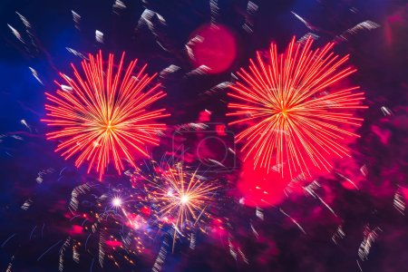 Photo pour Inexpensive fireworks over the city red, and yellow with colour smoke and sparks on the blue sky. Bright and shiny.  For any purpose. Celebration concept. - image libre de droit