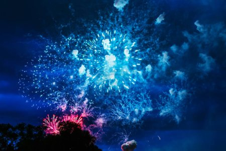 Photo pour Inexpensive fireworks over blue sky, red, green, blue and white with colour sparks. Selective focus. Bright and shiny. Celebration concept. - image libre de droit