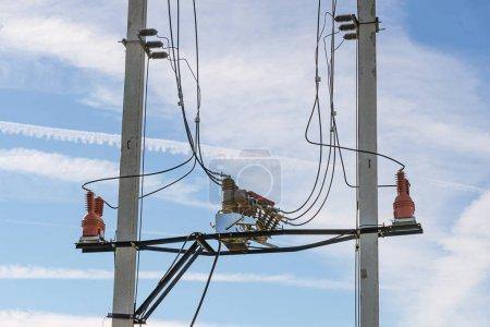 Photo pour Fusibles électriques à haute tension sur les piliers en béton gris avec isolateurs rouges sur le ciel bleu clair à l'arrière-plan - image libre de droit